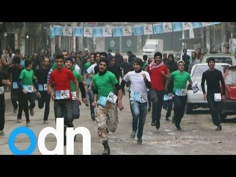 Runners race through rubble in war-torn city of Aleppo in Syria
