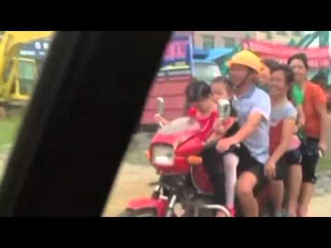 Overload: Motorbike with eight passengers drives along road in China