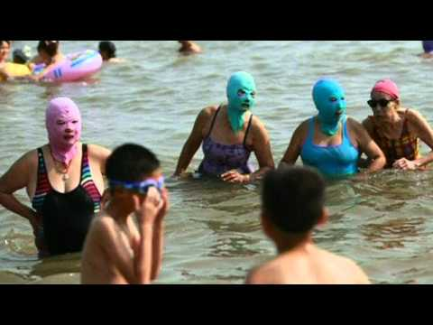 Chinese women wear facekinis to protect their skin on the beach