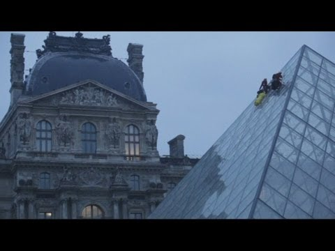 Activists scale the side of the Louvre Museum in Paris